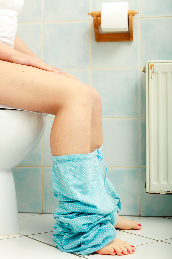 woman with constipation or diarrhoea sitting on toilet with gut condition